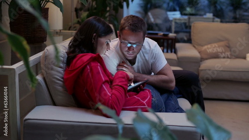 Young couple with tablet computer relaxing on sofa at home