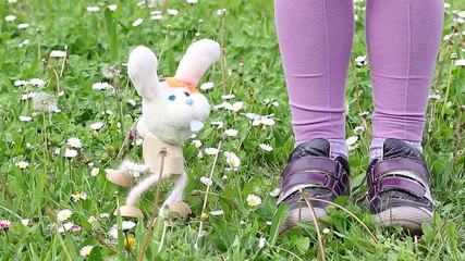 white rabbit marionette dancing on green grass
