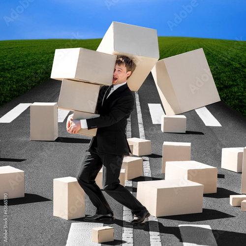 Shocked business man carrying carton boxes that fall down to the