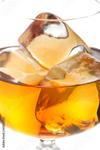 Whiskey with ice cubes in glass closeup