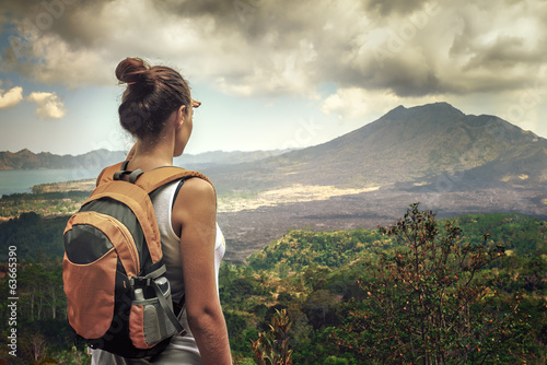 Lady tourist with a backpack standing on top of the mountain