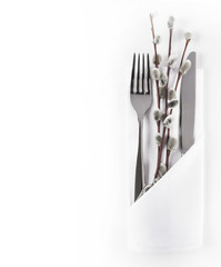 Silverware in white napkin envelope and willow