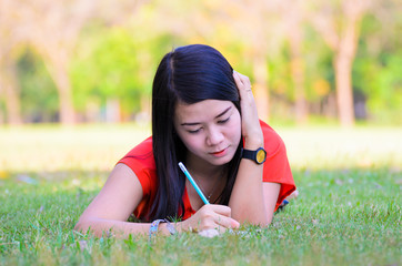 Portrait of a pretty young woman writing in her diary at outdoor