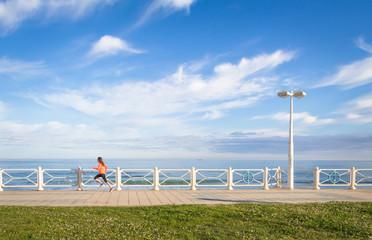 Young girl running in beach promenade on summer