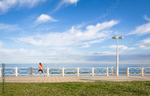 Young girl running in beach promenade on summer