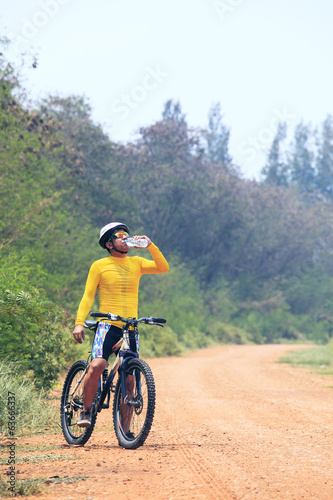 young bicycle (cyclist) man drinking fresh water from plastic bo