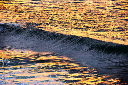 wave breaking at sunset