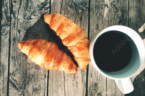 French croissants on a wooden table and black coffee cup
