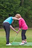 Golf pro teaching a lady golfer