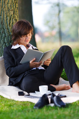 businesswoman reading outdoor in park