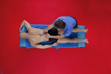 Overhead view of male therapist massaging muscular man back