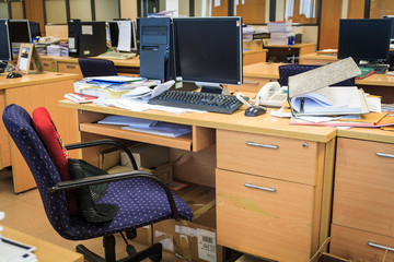Busy messy office consist of tables, computers, paper sheets