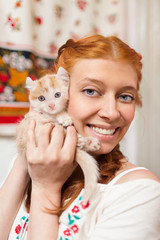 Red-haired girl with a red kitten