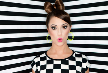 Attractive surprised young woman on stripes wallpaper