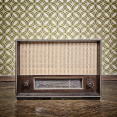 vintage radio receiver device on the weathered wooden parquet fl