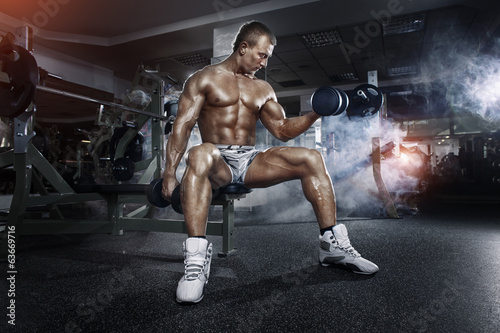Athlete in the gym training with dumbbells - 63669716