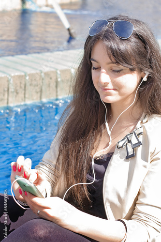 young girl listening  music with earphones in outdoor scene