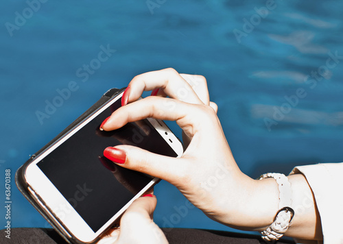 female fingers touching smartphone screen