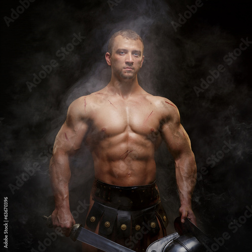 Gladiator standing in a smoke with helmet and sword
