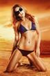 Luxurious blonde in a bikini on the beach at sunset
