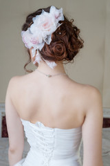 Portrait of back of bride in white dress with hair style and flo