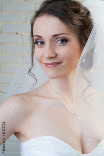 Happy smiling bride in white veil and dress