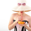 Beautiful pinup girl drinking juice of grapefruit in  sunglssses