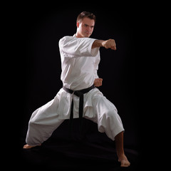 karate man with black belt posing, champion of the world on blac