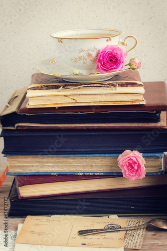pile of old books and mail with cup of tea