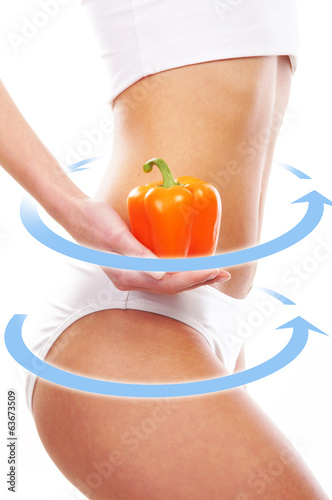 Beautiful belly of a woman holding a fresh paprika