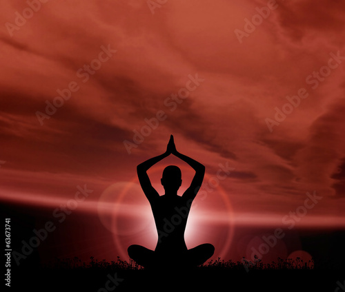 Silhouette of a young woman meditating outdoors
