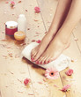 Spa background with beautiful legs, flowers and petals