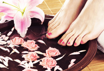 Spa background with beautiful feet, flowers and petals