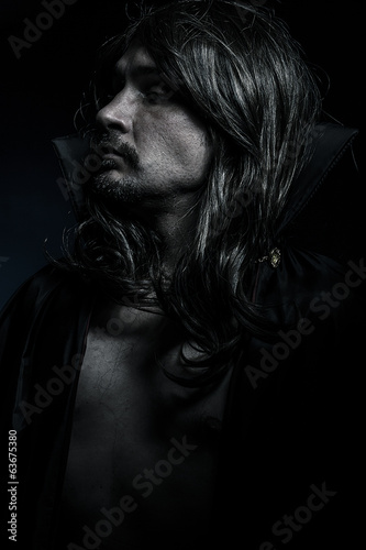 Vampire with black coat and long hair, blue light