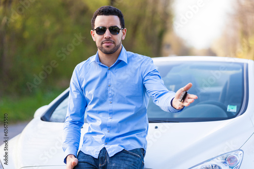 Young latin american driver holding car keys driving his new car
