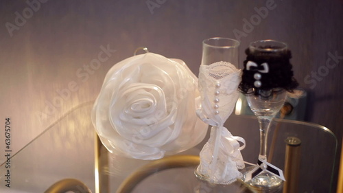 two glasses with champagne and bride's handbag on the table