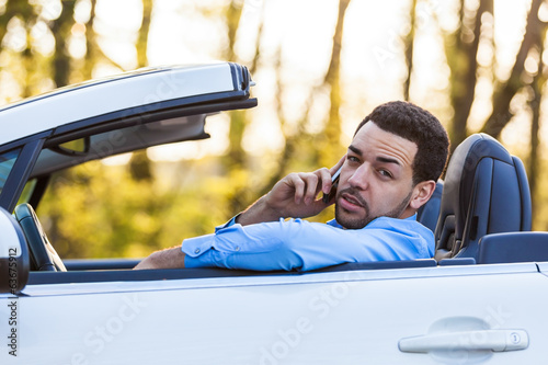 Young latin american driver making a phone call while driving