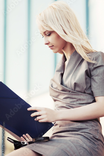 Young business woman holding financial folder