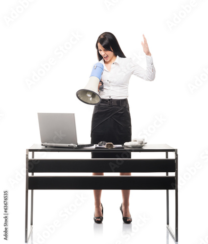 A usinesswoman screaming with a megaphone in an office
