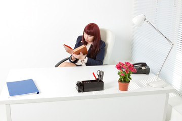 business woman in a modern office reading book