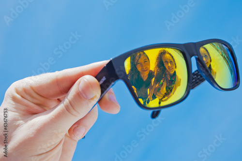 hand holding sunglasses on a blue background