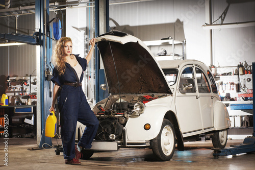 A young and sexy woman repairing a retro car