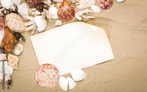 Sea shells on beach sand with old paper. Summer background