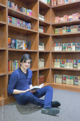 young student reading a book at the library