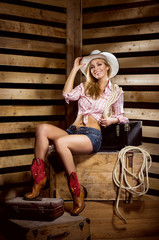 A young, happy and sexy cowgirl in western style