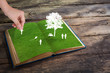 Paper cut of children play on green grass book