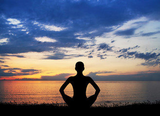 Sunset meditation. Silhouette of a woman doing yoga.