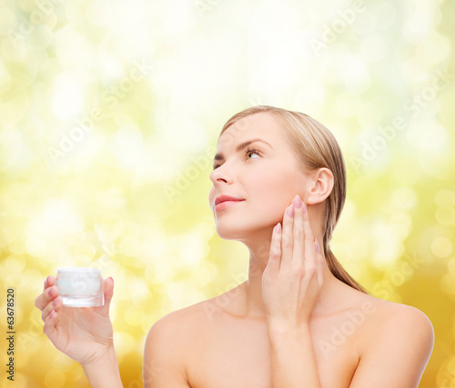 woman applying cream on her skin