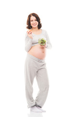 Happy pregnant woman with a salad isolated on white