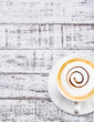 Coffee cup and saucer on white wood background